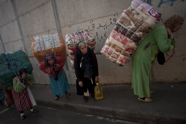 Women porters carry bundles on their backs for transport across the El Tarajal boarder separating Morocco and Spain's North African enclave of Ceuta, in Ceuta on December 4, 2014. (Photo by Jorge Guerrero/AFP Photo)