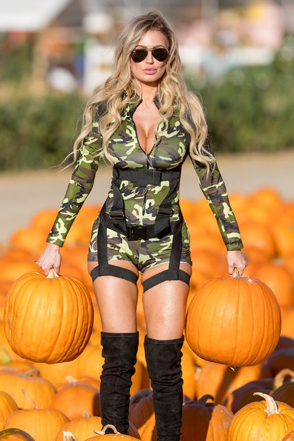 Brazilian Playmate Ana Braga goes camo commando at the pumpkin patch in Los Angeles, CA on October 20, 2016. (Photo by Splash News)