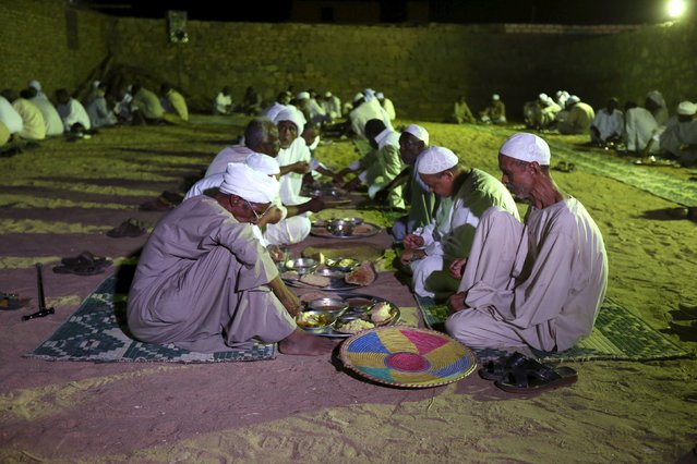 Invitees eat dinner as  people celebrate at a traditional Nubian wedding in the Nubian village of Adindan near Aswan, September 30, 2015. (Photo by Mohamed Abd El Ghany/Reuters)