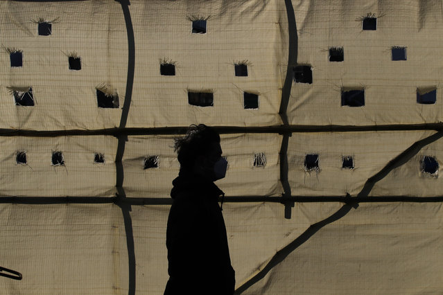 A man wearing a face mask as a precaution against the coronavirus is silhouetted as he walks past a construction site in Seoul, South Korea, Wednesday, December 16, 2020. (Photo by Lee Jin-man/AP Photo)
