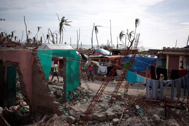 People walk in the street next to houses destroyed by Hurricane Matthew in Damassins, Haiti, October 22, 2016. REUTERS/Andres Martinez Casares