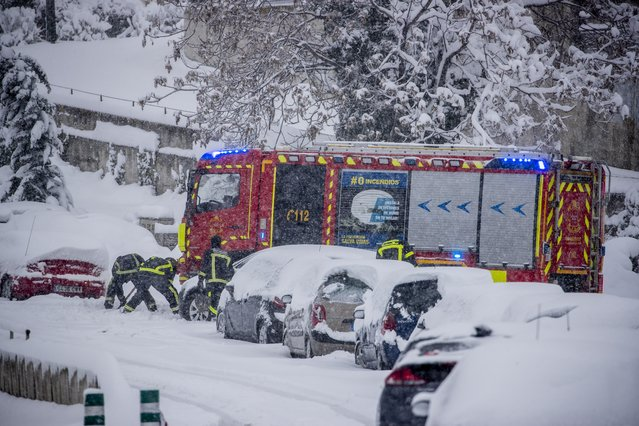 Firefighters work removing snow from a car during a heavy snowfall in Rivas Vaciamadrid, Spain, Saturday, January 9, 2021. An unusual and persistent blizzard has blanketed large parts of Spain with snow, freezing traffic and leaving thousands trapped in cars or in train stations and airports that had suspended all services as the snow kept falling on Saturday. The capital, Madrid, and other parts of central Spain activated for the first time its red weather alert, its highest, and called in the military to rescue people from cars vehicles trapped in everything from small roads to the city's major thoroughfares. (Photo by Manu Fernandez/AP Photo)