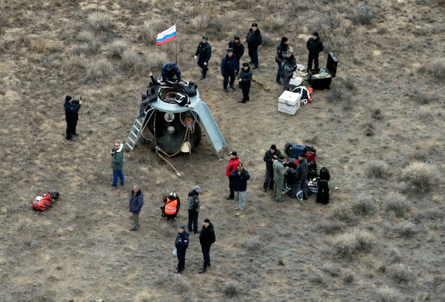 Specialists stand around the Russian Soyuz MS space capsule after its landing southeast of the town of Dzhezkazgan, Kazakhstan, Sunday, Oct. 30, 2016. (Photo by Dmitri Lovetsky/Reuters)