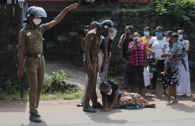 A family member of an inmate pleads lying at the feet of a policeman demanding to know the condition of her relative outside the Mahara prison complex following an overnight unrest in Mahara, outskirts of Colombo, Sri Lanka, Monday, November 30, 2020. Sri Lankan officials say six inmates were killed and 35 others were injured when guards opened fire to control a riot at a prison on the outskirts of the capital. Two guards were critically injured. Pandemic-related unrest has been growing in Sri Lanka's overcrowded prisons. (Photo by Eranga Jayawardena/AP Photo)