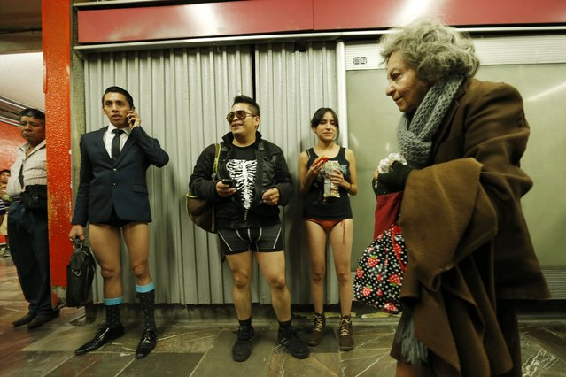 """A woman walks past passengers without pants waiting for the subway train during """"The No Pants Subway Ride"""" in Mexico City January 11, 2015. (Photo by Edgard Garrido/Reuters)"""