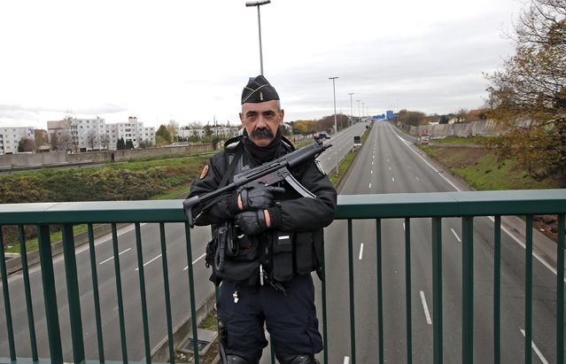 A French gendarme stands guard on a bridge which crosses over the empty lanes of the A1 motorway in Le Bourget, near Paris, France, November 30, 2015 due to heavy security during the opening day events at the World Climate Change Conference 2015 (COP21). (Photo by Eric Gaillard/Reuters)