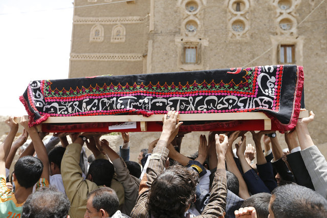 Mourners carry the coffin of a soldier, who was killed by al Qaeda militants in the Wadi Hadramout region in northeastern Yemen, during his funeral in Sanaa August 10, 2014. (Photo by Khaled Abdullah/Reuters)