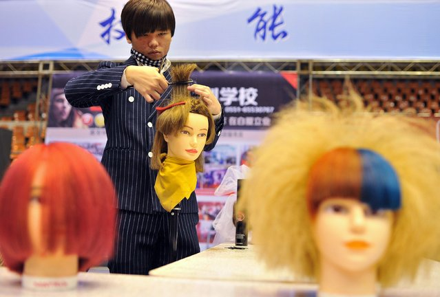 A barber demonstrates a haircut during a skilled worker festival in Hefei, Anhui province, January 16, 2015. (Photo by Reuters/Stringer)