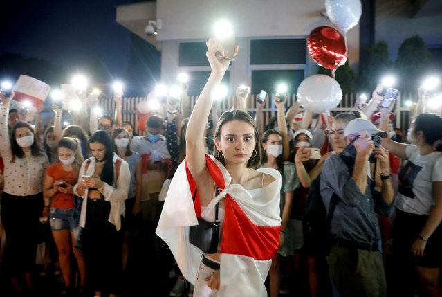 A demonstrator holds up her phone during a march in solidarity with Belarusian people after the presidential election, outside the Belarusian Embassy in Warsaw, Poland, August 14, 2020. (Photo by Kacper Pempel/Reuters)