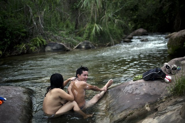 In this November 20, 2015 photo, Mary Palomino washes the back of her partner, Rober Vazquezok, in the river in Pichiquia, an Ashaninka indigenous community in Peru's Junin region. The rivers, most of them contaminated according to government authorities, are the only source of water for the Ashaninka. (Photo by Rodrigo Abd/AP Photo)
