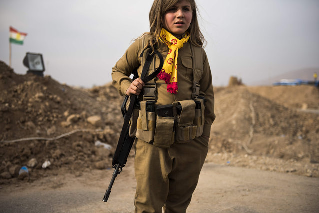 A Kurdish girl wears her relative's assault rifle and ammunition belt as she waits at the  Iraqi Kurdish Shaqouli checkpoint, some 35 kilometres east of Mosul, on November 10, 2016. Since the start of the Mosul offensive the Kurds have moved their border some 10 kms closer to Iraq's second city, marking it out with a line in the sand. (Photo by Odd Andersen/AFP Photo)