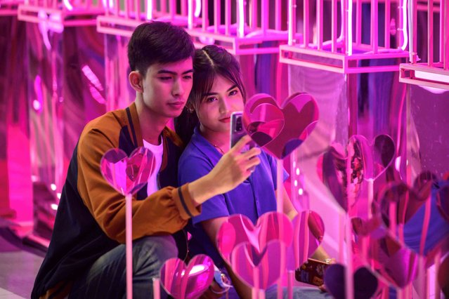 A couple takes selfie pictures amid heart shaped decorations setted for Valentine's day, in Bangkok, Thailand on February 14, 2021. (Photo by Mladen Antonov/AFP Photo)