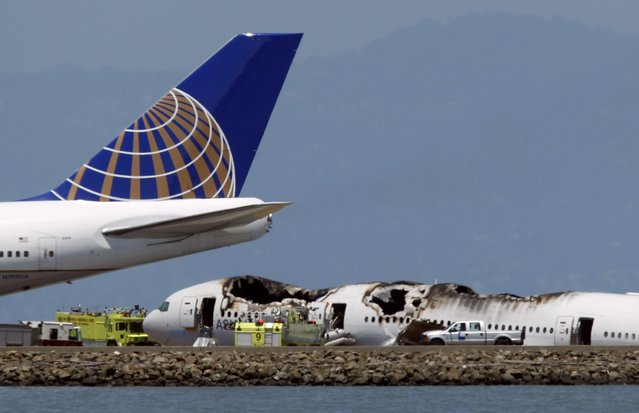A passenger plane taxis on the runway past an Asiana Airlines Boeing 777 that crashed while landing at San Francisco International Airport in San Francisco, California July 6, 2013. Two people were reported killed and 73 to 103 injured in the crash landing of the Asiana Airlines flight at San Francisco International Airport on Saturday, a city fire department dispatcher said. (Photo by Robert Galbraith/Reuters)