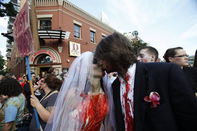 A couple dressed up as zombies kisses during a zombie walk in the Gaslamp Quarter during the Comic Con International convention in San Diego, California July 13, 2012. (Photo by Mario Anzuoni/Reuters)