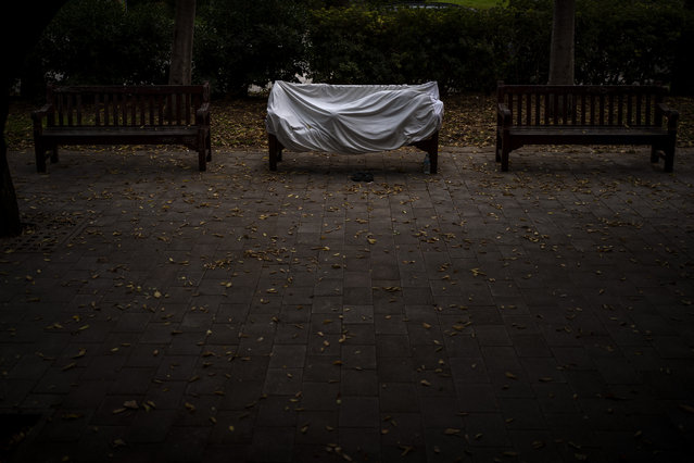 A homeless man covered by a sheet sleeps on a bench at a public park in Barcelona, Spain, Sunday, December 20, 2020. (Photo by Emilio Morenatti/AP Photo)