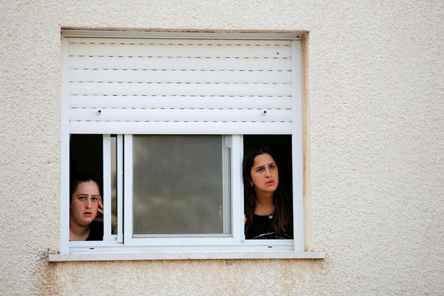Israeli teens look out of a window at the southern city of Sderot, on the Israeli side of the Israel – Gaza border July 14, 2018. (Photo by Amir Cohen/Reuters)