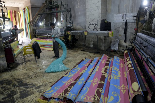 A man prepares plastic strings, used to produce mats, inside a mat factory in the rebel-controlled area of Maarshureen town in Idlib province, Syria, December 22, 2015. The town is known for the significant number of mat factories which exports its production mainly to nearby Iraq through checkpoints controlled by insurgents. But in the past months the business has declined due to heavy airstrikes against insurgents, vendors said. (Photo by Khalil Ashawi/Reuters)