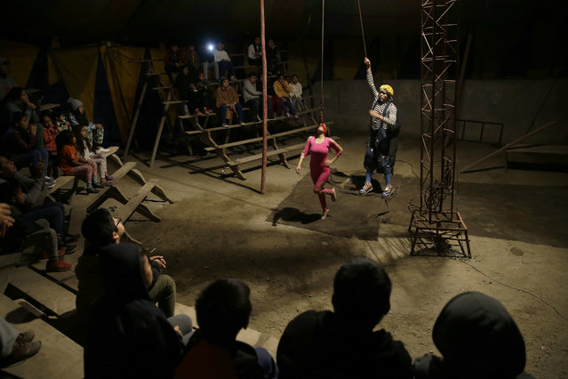 """In this July 8, 2018 photo, """"Vaguito"""" the clown assists acrobat Brenda Aguila as she prepares to hang from her head, as spectators watch the Tony Perejil circus, set up in the shanty town of Puente Piedra on the outskirts of Lima, Peru. The circus owner, Jose Alvarez, said he remembers happier times in the 1980s, when his father filled their circus tent with people even though Peru was in the midst of an economic crisis and a war raged between the state and Sendero Luminoso guerrillas. (Photo by Martin Mejia/AP Photo)"""