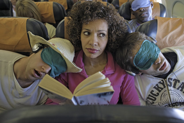 Woman sat on plane two men asleep on her shoulders. (Photo by Peter Cade/Getty Images)
