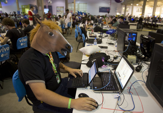 A man wears a horse mask during the Campus Party technology festival in Sao Paulo, Brazil, Tuesday, February 3, 2015. Campus Party is an annual week-long, 24-hour technology festival that gathers hackers, developers, gamers and computer enthusiasts. (Photo by Andre Penner/AP Photo)