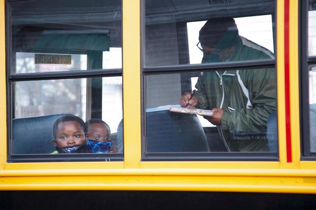 The bus driver verifies the names of Esther Bahome and Mmema Mkangya on their first day back to school after coronavirus disease (COVID-19) restrictions were adjusted, in Louisville, Kentucky, U.S. March 17, 2021. (Photo by Amira Karaoud/Reuters)