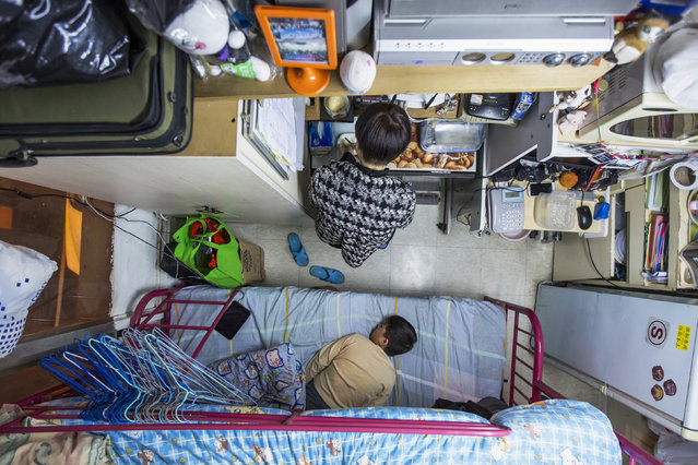 A woman and her son are seen in their 60-square-foot sub-divided flat, with a monthly rent of HK$3,800 ($487), in Hong Kong February 2, 2015. (Photo by Tyrone Siu/Reuters)