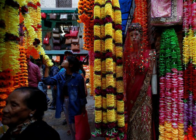 A customer looks at the garlands kept on sale for the Tihar festival, also called Diwali, along the streets of Kathmandu, Nepal, October 26, 2016. (Photo by Navesh Chitrakar/Reuters)