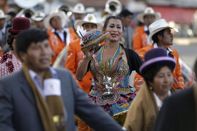 """In this Sunday, August 5, 2018 photo, transgender Paloma, dressed as a dancer known as a """"china"""" for the """"Morenada"""" or Dance of the Black Slaves, takes part in a religious procession in honor of Our Lady of Copacabana, in Cuzco, Peru. A group of transsexual activists in Cuzco have adopted the Bolivian virgin as their patron saint. (Photo by Martin Mejia/AP Photo)"""