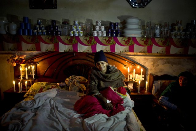 In this Sunday, February 1, 2015 photo, Pakistani Christian Shanaz Rafiq, 28, rests on her bed holding her 5 day-old son who was named Ashber after his baptism ceremony, upon her arrival from a hospital to her home in Rawalpindi, Pakistan. (Photo by Muhammed Muheisen/AP Photo)