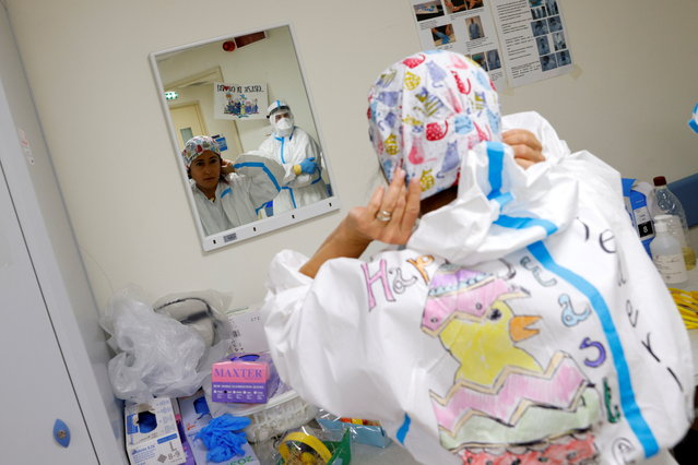 A medical worker wearing protective equipment (PPE) decorated with Easter themed drawings gets ready before starting her shift at the San Filippo Neri hospital, where patients suffering from the coronavirus disease (COVID-19) are being treated in Rome, Italy, April 4, 2021. (Photo by Guglielmo Mangiapane/Reuters)