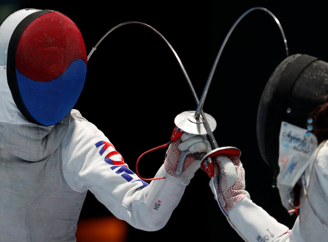 South Korea' s Hee Sook Jeon, left, competes against Japan' s Sera Azuma, right, during their women foil individual fencing match at the 18 th Asian Games in Jakarta, Indonesia, Monday, August 20, 2018. (Photo by Reuters/Beawiharta)
