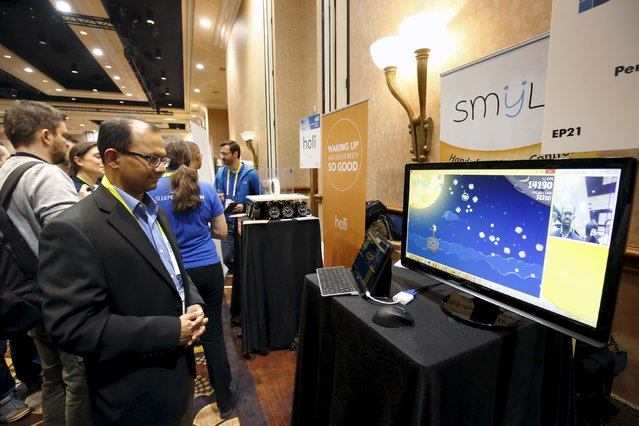"""Uday Parshionikar (L), founder and CEO of Perceptive Devices, demonstrates the Smyle gesture control software as he plays Angry Birds during """"CES Unveiled,"""" a preview event of the 2016 International CES trade show, in Las Vegas, Nevada January 4, 2016. The system uses your facial expression, in place of a mouse, to move and click. The system has applications for able-bodied people as well as people with disabilities, he said. (Photo by Steve Marcus/Reuters)"""