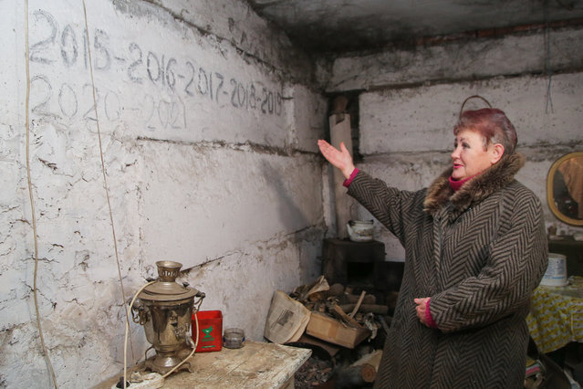 A woman points to dates written on the wall in a bomb shelter in Yasinovatya (Yasynuvata) in Donetsk Region, Ukraine on March 24, 2021. The dates refer to New Year's parties that she and other local people celebrated in the bomb shelter. Due to military escalation all along the line of contact between the forces of the Donetsk People's Republic and the Ukrainian government's forces, people in the Donetsk People's Republic started checking if their bomb shelters.are ready to be used. Some people are still living in bomb shelters because the hostilities have left them homeless. The military conflict in east Ukraine broke out in 2014. (Photo by Valentin Sprinchak/TASS)