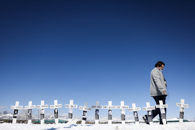 Tyler Vielie walks past crosses with the names of the victims of the Columbine High School shooting next to the Columbine Memorial on April 20, 2021 in Littleton, Colorado. Twelve students and a teacher were killed in the mass shooting 22 years ago today, which at the time was the deadliest school shooting in US history. (Photo by Michael Ciaglo/Getty Images)