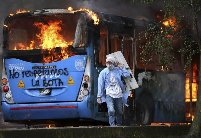 A man walks in front of a public transportation bus in flames during a protest against a tax reform bill launched by Colombian President Ivan Duque, in Cali, on April 28, 2021. Workers' unions, teachers, civil organizations, indigenous people and other sectors reject the project that is underway in the Congress, considering that it punishes the middle class and is inappropriate in the midst of the crisis unleashed by the COVID-19 pandemic. (Photo by Paola Mafla/AFP Photo)