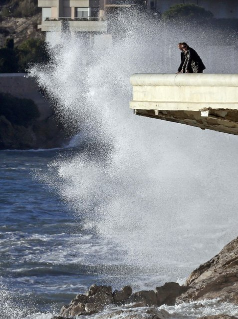 Passers-by look at a high wave that hits the waterfront in Marseille, France as stormy weather with high winds hits part of the French Mediterranean coast January 11, 2016. (Photo by Jean-Paul Pelissier/Reuters)