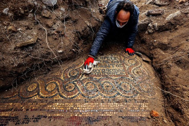 Izmir Archeology Museum experts inspect a 1500-year-old mosaic after it was discovered in a Roman-era monastery at Aliaga district in Izmir, Turkey on April 2, 2021. (Photo by Mehmet Emin Menguarslan/Anadolu Agency via Getty Images)