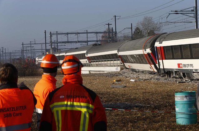 Rescue workers stand next to a derailed train after two trains collided near Rafz around 30 km (18 miles) from Zurich February 20, 2015. Two passenger trains collided in Switzerland on Friday, causing five injuries and disrupting commuter routes into Zurich, police and rail operator SBB said. (Photo by Arnd Wiegmann/Reuters)