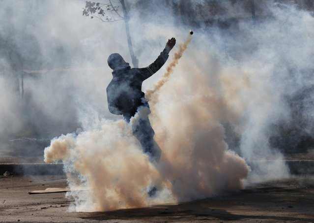 A Palestinian protester hurls back a tear gas canister fired by Israeli troops during clashes in the West Bank city of Bethlehem January 13, 2016. (Photo by Ammar Awad/Reuters)