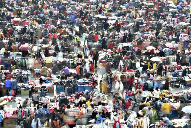 People shop at a garment market ahead of the upcoming Spring Festival, in Hangzhou, Zhejiang province, February 14, 2015. (Photo by Reuters/Stringer)