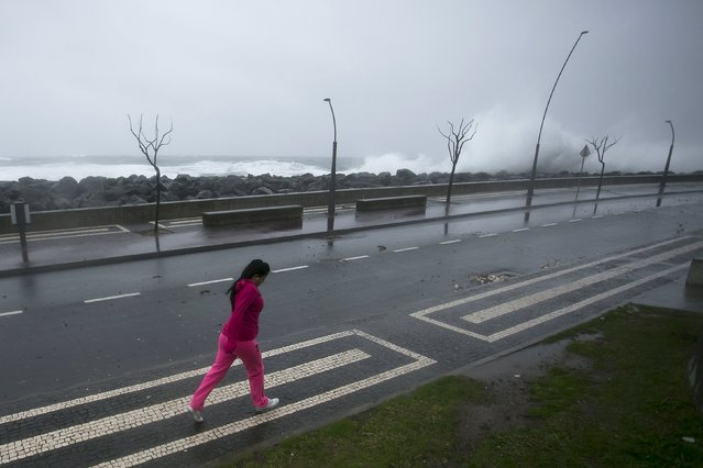 A woman walks on the street during the passage of hurricane Alex in Ponta Delgada, Azores, Portugal, January 15, 2016. (Photo by Rui Soares/Reuters)