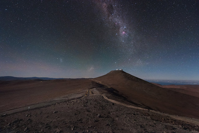 The landscape surrounding ESO's Very Large Telescope (VLT) in Chile is almost reminiscent of an alien world. The tiny silver shapes on the distant Cerro Paranal mountain are the VLT's Unit Telescopes (UTs) and smaller Auxiliary Telescopes (ATs). This image is taken from the nearby mountain that is home to another of ESO's facilities, the Visible and Infrared Survey Telescope for Astronomy (VISTA). (Photo by Y. Beletsky/ESO)
