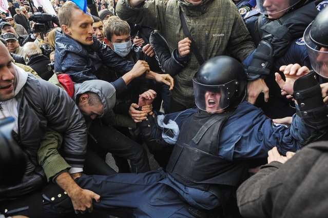 Ukrainian opposition activists clash with riot police as they attempt to get into the mayoral office during a rally against the Kiev mayoral election, which was earlier postponed until 2015, in Kiev, on October 2, 2013. (Photo by Maks Levin/Reuters)