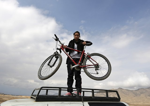 Zhala, a member of Afghanistan's Women's National Cycling Team, unloads her bicycle as she arrives at a training area on the outskirts of Kabul February 20, 2015. (Photo by Mohammad Ismail/Reuters)