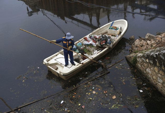 A worker collects rubbish on a drainage canal in Hanoi on February 26, 2021. (Photo by Nhac Nguyen/AFP Photo)