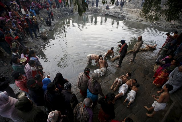 People gather around as devotees offer prayers by rolling near the riverbank of Hanumante River before submerging themselves in the river during a month-long Swasthani Brata Katha festival in Bhaktapur, Nepal, January 27, 2016. During a month-long festival, devotees recite one chapter of a Hindu tale daily from the 31-chapter sacred Swasthani Brata Katha book that is dedicated to God Madhavnarayan and Goddess Swasthani, alongside various other gods and goddess and the miraculous feats performed by them. (Photo by Navesh Chitrakar/Reuters)