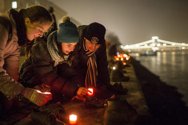 Backdropped of the illuminated Castle Hill and the Chain Bridge, people light candles in front of the cast iron shoes Holocaust Memorial on the quay of the River Danube during a commemoration marking the International Holocaust Remembrance Day in Budapest, Hungary, 27 January 2016. International Holocaust Remembrance Day marks the liberation of Auschwitz-Birkenau nazi concentration camp by Soviet troops on 27 January 1945. (Photo by Balazs Mohai/EPA)