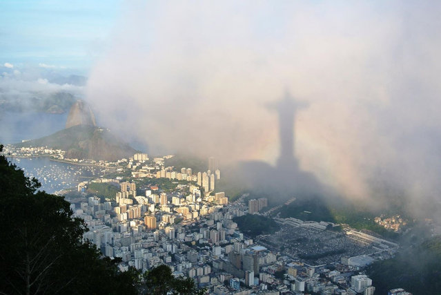 """Ben Goodwin, August winner. """"Rio de Janeiro as seen from Corcovado, with the shadow of Christ the Redeemer projected onto the clouds and framed by a rainbow"""". MICK RYAN, JUDGE: What perfect timing, and not just because of the Olympics. Landscape photography is often dependent on light and weather for that wow factor, and being in the right place at the right time. This dramatic image, taken early morning with the light shining through the mist, produces a broken spectre – a rainbow shadow – of the statue. It must have taken some planning and effort to get such a wonderful photograph. (Photo by Ben Goodwin/The Guardian)"""