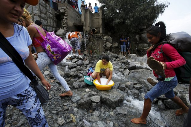 A woman does her laundry as people cross a flooded street after a massive landslide in Chosica, March 24, 2015. (Photo by Mariana Bazo/Reuters)