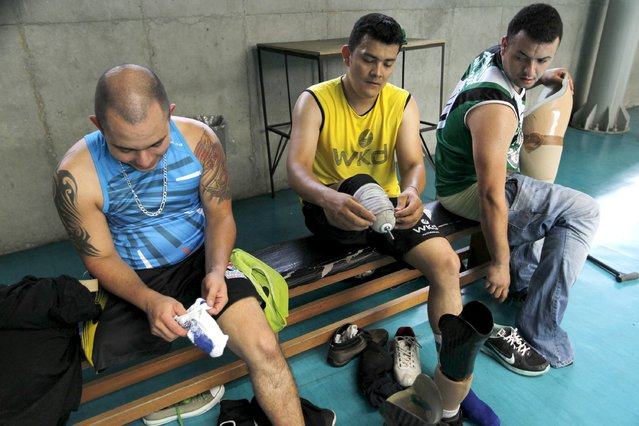 National Army of Colombia soldiers, who were wounded by mines, change after playing sitting volleyball in Bello, municipality of Antioquia, March 25, 2015. (Photo by Fredy Builes/Reuters)